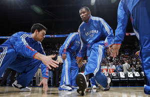photo - Oklahoma City's Kevin Durant is greeted by teammates, including Nick Collison, left, as Durant is introduced before the NBA basketball game between the Washington Wizards and the Oklahoma City Thunder at the Oklahoma City Arena in Oklahoma City, Friday, January 28, 2011. The Thunder won, 124-117, in double overtime. Photo by Nate Billings, The Oklahoman