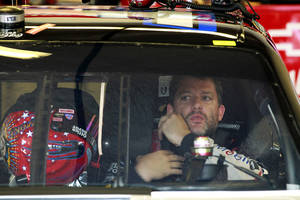 Photo -   Tony Stewart adjusts his safety equipment before going out on the track during practice for the NASCAR Sprint Cup Series Coke Zero 400 auto race at Daytona International Speedway, Thursday, July 5, 2012, in Daytona Beach, Fla. (AP Photo/John Raoux)