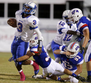 Photo - Millwood's Cameron Montgomery tries to get past Christian Heritage Academy's Jacob Files during their high school football game at Christian Heritage in Oklahoma City, Friday, Oct. 4, 2013. Photo by Bryan Terry, The Oklahoman