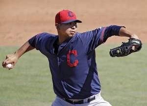 Photo - Cleveland Indians starting pitcher Carlos Carrasco delivers against the Cincinnati Reds in the sixth inning of a spring exhibition baseball game Monday, March 24, 2014, in Goodyear, Ariz. (AP Photo/Mark Duncan)