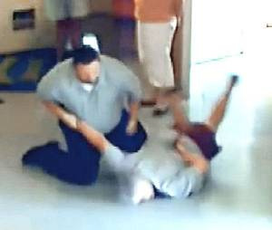 Photo - ARREST: Wister Police Chief Chris Ford taking Brenda Smith, 50, to the ground on July 13. She was subsequently arrested for using profanity and resisting arrest.  These are from a video obtained from a city hall security video. ORG XMIT: KOD