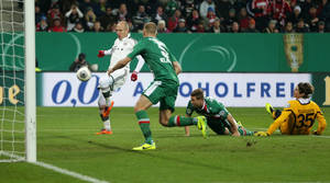 Photo - Bayern's Arjen Robben of the Netherlands, left, scores his side's opening goal during the German soccer cup third round match between FC Augsburg and FC Bayern Munich in Augsburg, southern Germany, Wednesday, Dec. 4, 2013. (AP Photo/Matthias Schrader)