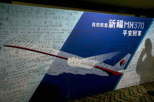 """Photo - FILE - In this March 24, 2014 file photo, the shadow of a man using his mobile phone falls on a board with the characters """"Pray for MH370 safe return"""" meant for relatives and workers to write their prayers and well wishes in a room reserved for relatives of Chinese passengers aboard the missing Malaysia Airlines flight 370 in Beijing, China. Relatives of five people on board the missing Malaysian jetliner are trying to crowd source a $5 million reward for information about what happened to the plane. The group says it """"wants to provide a substantial incentive for anyone who knows the truth to come forward."""" The Boeing 777 disappeared on March 8 while carrying 239 people from Malaysia to Beijing. (AP Photo/Ng Han Guan, File)"""