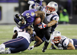 Photo - Baltimore Ravens running back Bernard Pierce (30) is tackled by New England Patriots free safety Devin McCourty, left, and New England Patriots cornerback Logan Ryan in the first half of an NFL football game, Sunday, Dec. 22, 2013, in Baltimore. (AP Photo/Nick Wass)