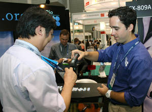 Photo - Steven Martinez, right, co-director of the Small Business Innovation Research program at Oklahoma Center for the Advancement of Science and Technology, scans the badge of a visitor to the Oklahoma booth at the BIO International Convention this week in Boston. PHOTO BY JIM STAFFORD, For The Oklahoman