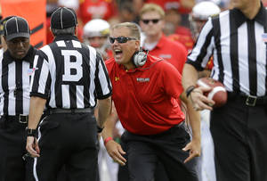 Photo - Maryland head coach Randy Edsall, center, argues a penalty call with officials in the first half of an NCAA college football game against Old Dominion in College Park, Md., Saturday, Sept. 7, 2013. Maryland gained possession after defensive back Sean Davis intercepted a pass, but his touchdown was reversed after Maryland received a penalty for blocking from the back on the play. (AP Photo/Patrick Semansky)