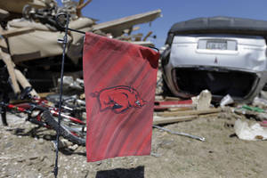 Photo - An Arkansas Razorback flag hangs in front of a home destroyed by Sunday's tornado, Tuesday, April 29, 2014, in Vilonia, Ark. A dangerous storm system that spawned a chain of deadly tornadoes over two days flattened homes and businesses, and killed dozens from the Midwest to the Deep South. (AP Photo/Eric Gay)