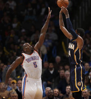 Photo - Oklahoma City's Kendrick Perkins (5) defends against Indiana's Paul George (24) during the NBA game between the Oklahoma City Thunder and the Indiana Pacers at the Chesapeake Energy Arena, Sunday, Dec. 8, 2013. Photo by Sarah Phipps, The Oklahoman