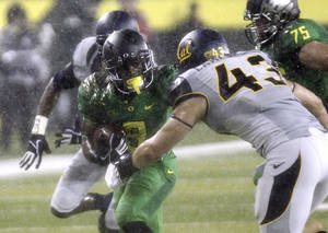 Photo - Oregon running back Byron Marshall, left, tries to evade California defender Dan Camporeale during the first half of an NCAA college football game in Eugene, Ore., Saturday, Sept. 28, 2013. (AP Photo/Don Ryan)