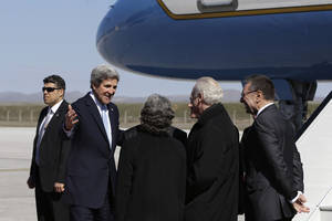 Photo - U.S. Secretary of State John Kerry gestures as he is greeted upon arrival Ankara, Turkey, on Friday, March 1, 2013. Ankara is the fifth leg of Kerry's first official overseas trip, a nine-day dash through Europe and the Middle East. (AP Photo/Jacquelyn Martin, Pool)