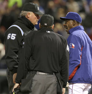 Photo - Texas Rangers manager Ron Washington, right, argues a call with umpires Ted Barrett (65) and Paul Schrieber during the sixth inning of a baseball game against the Seattle Mariners Monday, April 14, 2014, in Arlington, Texas. Washington was ejected from the game after the call was made. (AP Photo/LM Otero)
