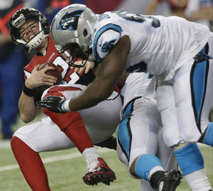 Photo - Atlanta Falcons quarterback Matt Ryan (2) is sacked by Carolina Panthers defensive end Greg Hardy (76) and Carolina Panthers defensive end Charles Johnson (95) during the second half of an NFL football game, Sunday, Dec. 29, 2013, in Atlanta. (AP Photo/Dave Martin)