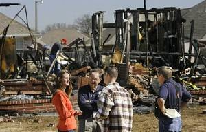 photo - Winston Barton, center, talks to Valerie and Matt Waxenfelter in front of a destroyed home in the Oakwood East Royale neighborhood Tuesday morning. By Jim Beckel.