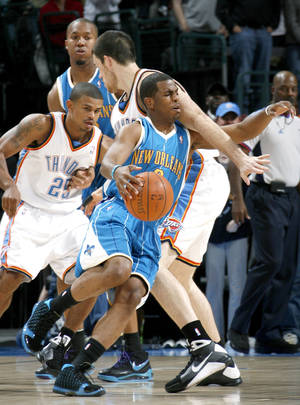 photo - Chris Paul of New Orleans get tangled up with Nick Collison of Oklahoma City during the NBA basketball game between the Oklahoma City Thunder and the New Orleans Hornets at the Ford Center in Oklahoma City on Friday, Nov. 21, 2008.  By Bryan Terry
