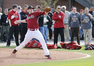 Photo - Arizona Diamondbacks pitcher Archie Bradley runs drills during the teams first baseball spring training workout, Friday, Feb. 7, 2014, in Scottsdale, Ariz. (AP Photo/Matt York)