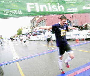 Photo - Jordan Hoehne reacts as he crosses the finish line in the half marathon during the 11th Annual Oklahoma City Memorial Marathon in Oklahoma City on Sunday, May 1, 2011. Photo by John Clanton, The Oklahoman