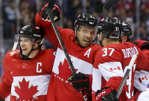 Photo - Canada defenseman Shea Weber, center, celebrates with forward Sidney Crosby, left, and forward Patrice Bergeron after scoring a goal against Norway in the second period of a men's ice hockey game at the 2014 Winter Olympics, Thursday, Feb. 13, 2014, in Sochi, Russia. (AP Photo/Julio Cortez)