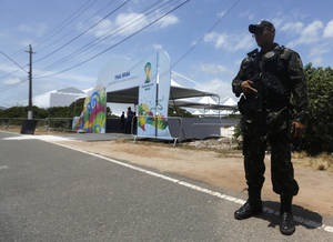 Photo - A soldier secures the entrance of the draw hall one day before the draw for the 2014 soccer World Cup in Costa do Sauipe near Salvador, Brazil, Thursday, Dec. 5, 2013. (AP Photo/Victor Caivano)