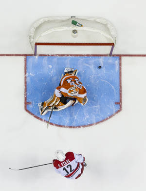 Photo - Carolina Hurricanes' Eric Staal, bottom, shoots the puck past Philadelphia Flyers' Cal Heeter, top, for a goal during the shootout of an NHL hockey game, Sunday, April 13, 2014, in Philadelphia. The Hurricanes won 6-5. (AP Photo/Chris Szagola)