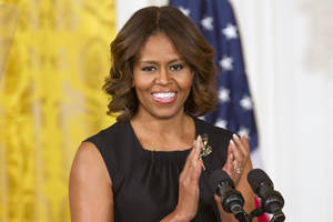 "Photo - First lady Michelle Obama applauds in the East Room of the White House in Washington, Wednesday, June 4, 2014, during a Joining Forces initiative event to announce ""The Mayors Challenge to End Veteran Homelessness"" program. (AP Photo/Jacquelyn Martin)"