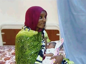 Photo - FILE - In this file image made from an undated video provided Thursday, June 5, 2014, by Al Fajer, a Sudanese nongovernmental organization, Meriam Ibrahim breastfeeds her newborn baby girl that she gave birth to in jail last week, as the NGO visits her in a room at a prison in Khartoum, Sudan. Sudan's official news agency, SUNA, said the Court of Cassation in Khartoum on Monday, June 23, canceled the death sentence against 27-year-old Meriam Ibrahim after defense lawyers presented their case. The court ordered her release. (AP Photo/Al Fajer, File)