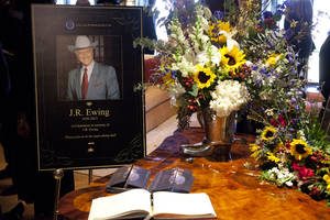 """Photo - This image released by TNT shows a funeral scene for the character J.R. Ewing, played by Larry Hagman, in an episode of """"Dallas,"""" airing Monday at 9 p.m. EST on TNT. Hagman died of cancer at 81 the day after Thanksgiving.  (AP Photo/TNT, Skip Bolen)"""