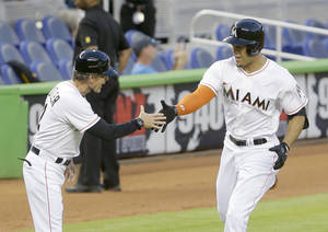 Photo - Miami Marlins' Giancarlo Stanton, right, is congratulated by third base coach Brett Butler as he rounds third base during the first inning of a baseball game against the San Diego Padres, Friday, April 4, 2014, in Miami. (AP Photo/Wilfredo Lee)