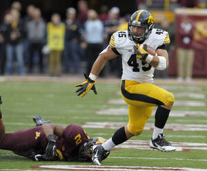 Photo - Iowa fullback Mark Weisman (45) leaves behind Minnesota defensive back Cedric Thompson (2) on a 14-yard gain during the fourth quarter of an NCAA college football game in Minneapolis Saturday, Sept. 28, 2013. Iowa beat Minnesota 23-7. (AP Photo/Ann Heisenfelt)