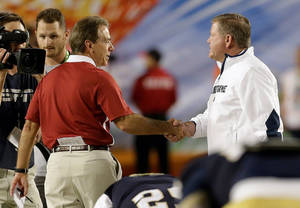 photo - Alabama head coach Nick Saban, left, shakes hands with Notre Dame head coach Brian Kelly before the BCS National Championship college football game Monday, Jan. 7, 2013, in Miami. (AP Photo/Chris O'Meara)
