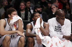 Photo - Brooklyn Nets forward Brook Lopez, left, guard Joe Johnson, center, and forward Kevin Garnett sit on the bench during  the second half of an NBA basketball game against the Denver Nuggets, Tuesday, Dec. 3, 2013, in New York. The Nuggets won 111-87. (AP Photo/Kathy Willens)