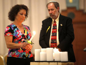 Photo - Frances Stewart lights a candle during the 21st annual Holocaust Commemoration service Tuesday at the Civic Center Music Hall in Oklahoma City. <strong>SARAH PHIPPS - SARAH PHIPPS</strong>