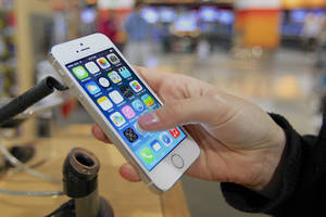 Photo - A customer examines a new iPhone 5s at the Nebraska Furniture Mart in Omaha, Neb., on Friday, Sept. 20, 2013, the day the new iPhone 5c and 5s models go on sale. (AP Photo/Nati Harnik) ORG XMIT: NENH102