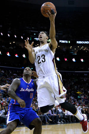 Photo - New Orleans Pelicans forward Anthony Davis (23) drives past Los Angeles Clippers forward Glen Davis (0) during the second half of an NBA basketball game in New Orleans, Wednesday, March 26, 2014. The Pelicans won 98-96. (AP Photo/Jonathan Bachman)