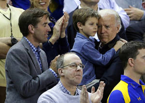 Photo - Vice President Joe Biden, right, holds his grandson Hunter next to his son, Beau, while watching a second-round game between Delaware and North Carolina in the women's NCAA college basketball tournament in Newark, Del., Tuesday, March 26, 2013. (AP Photo/Patrick Semansky)