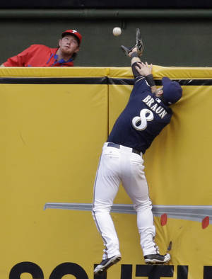 Photo - Milwaukee Brewers' Ryan Braun can't catch a two-run home run hit by Philadelphia Phillies' Chase Utley during the first inning of a baseball game Monday, July 7, 2014, in Milwaukee. (AP Photo/Morry Gash)