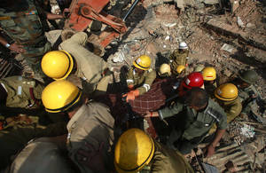 Photo - Rescue workers carry the body of a victim amid the debris of a building that collapsed in Canacona, a city about 70 kilometers (44 miles) from Goa state capital Panaji, India, Sunday, Jan. 5, 2014. A five-story building under construction in the southern Indian state of Goa collapsed on Saturday, killing at least a dozen people and leaving dozens more feared trapped under the rubble, police said. (AP Photo/Rafiq Maqbool)