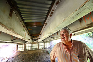 Photo - McClain County District 2 Commissioner Wilson Lyles stands beneath a bridge near Washington, OK, that was built using beams from the old Interstate 40 Crosstown Expressway. Photo BY  DAVID MCDANIEL,  THE OKLAHOMAN