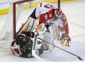 Photo - Ottawa Senators center Jean-Gabriel Pageau, bottom, crashes into Florida Panthers goalie Scott Clemmensen during first-period NHL hockey game action on Thursday, Dec. 19, 2013, in Ottawa, Ontario. (AP Photo/The Canadian Press, Adrian Wyld)
