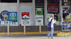Photo - A student walks past cigarette and beer sign in a convenience store near her school on north May, Friday, March 28, 2008.  Photo by DAVID MCDANIEL, THE OKLAHOMAN