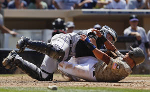 Photo -   San Diego Padres' Everth Cabrera, bottom, slides hard into Colorado Rockies catcher Jordan Pacheco while scoring on a single by John Baker during the fourth inning of a baseball game on Sunday, July 22, 2012, in San Diego. (AP Photo/Lenny Ignelzi)