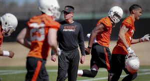 Photo - Oklahoma State head football coach Mike Gundy looks on as his team takes to the field during the first day of spring football practice at Oklahoma State University in Stillwater, Okla., on Monday, March 10, 2014.  Photo by Chris Landsberger, The Oklahoman