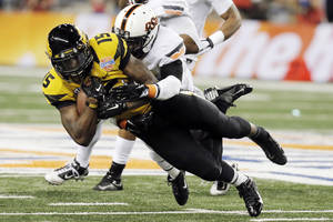 Photo - FILE - In this Jan. 3, 2014, file photo, Missouri wide receiver Dorial Green-Beckham (15) is tackled by Oklahoma State safety Daytawion Lowe during the second half of the Cotton Bowl NCAA college football game in Arlington, Texas. Green-Beckham has been suspended indefinitely for an unspecified violation of team rules, three months after he and two friends were arrested on suspicion of felony drug distribution. Coach Gary Pinkel announced the suspension Monday, April 7, in a brief news release. (AP Photo/Brandon Wade, File)
