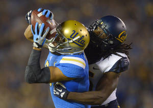 Photo - UCLA wide receiver Jordan Payton, left, makes a catch for 43 yards as California defensive back Adrian Lee tackles him during the first half of their NCAA college football game, Saturday, Oct. 12, 2013, in Pasadena, Calif. (AP Photo/Mark J. Terrill)
