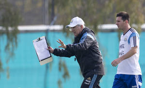 Photo - Argentina's coach Alejandro Sabella, left, gives instructions as player Lionel Messi walks behind during a team training session in Buenos Aires, Argentina, Wednesday, May 28, 2014. Argentina is training for the World Cup that starts in June in Brazil. (AP Photo/Natacha Pisarenko)
