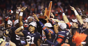 Photo - Auburn running back and SEC MVP Tre Mason (21) celebrates with teammates as they hoist the SEC Championship Trophy following the victory over Missouri in the SEC Championship Game at Georgia Dome in Atlanta, Ga. on Saturday Dec. 7, 2013. (AP Photo/Mickey Welsh, Montgomery Advertiser)