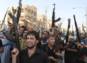 Photo - Shiite tribal fighters raise their weapons and chant slogans against the al-Qaida-inspired Islamic State of Iraq and the Levant (ISIL) in the northwest Baghdad's Shula neighborhood, Iraq, Monday, June 16, 2014. Sunni militants captured a key northern Iraqi town along the highway to Syria early on Monday, compounding the woes of Iraq's Shiite-led government a week after it lost a vast swath of territory to the insurgents in the country's north. (AP Photo/ Karim Kadim)