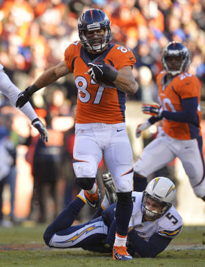 Photo - Denver Broncos wide receiver Eric Decker (87) slips away from San Diego Chargers punter Mike Scifres (5) on a return in the second quarter of an NFL AFC division playoff football game, Sunday, Jan. 12, 2014, in Denver. Scifres was injured on the play. (AP Photo/Jack Dempsey)