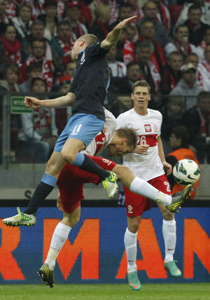Photo -   England's Tom Cleverley left is challenged by Poland's Eugen Polanski ,center, and Lukasz Piszczek during their World Cup Group H qualifying soccer match at National Stadium in Warsaw, Poland, Wednesday, Oct. 17, 2012 (AP Photo/Czarek Sokolowski