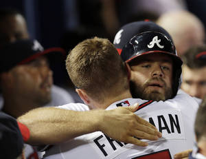 Photo - Atlanta Braves pinch hitter Evan Gattis, right,  hugs teammate Freddie Freeman after hitting a game-tying home run in the ninth inning of a baseball game against the Minnesota Twins Tuesday, May 21, 2013 in  in Atlanta. Atlanta won 5-4 in ten innings. (AP Photo/John Bazemore)