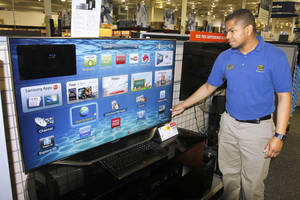 Photo - Walter Holland, home theater manager for Best Buy at 5801 N May, demonstrates a 60-inch Samsung Smart TV, one of the store's biggest sellers leading up to the Super Bowl. Viewers can track fantasy leagues on the screen while watching the game.